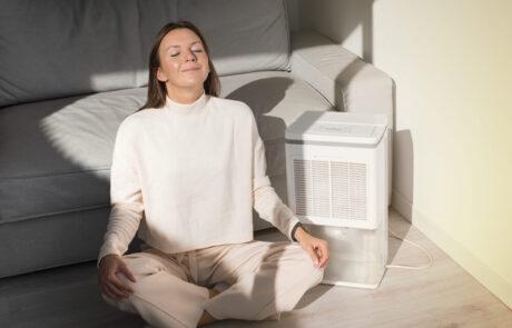 Žena sedi pored Jonizator vazduha u stanu